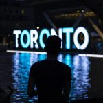 word Toronto in neon lights in background, shadow of a person in darkness in front of sign